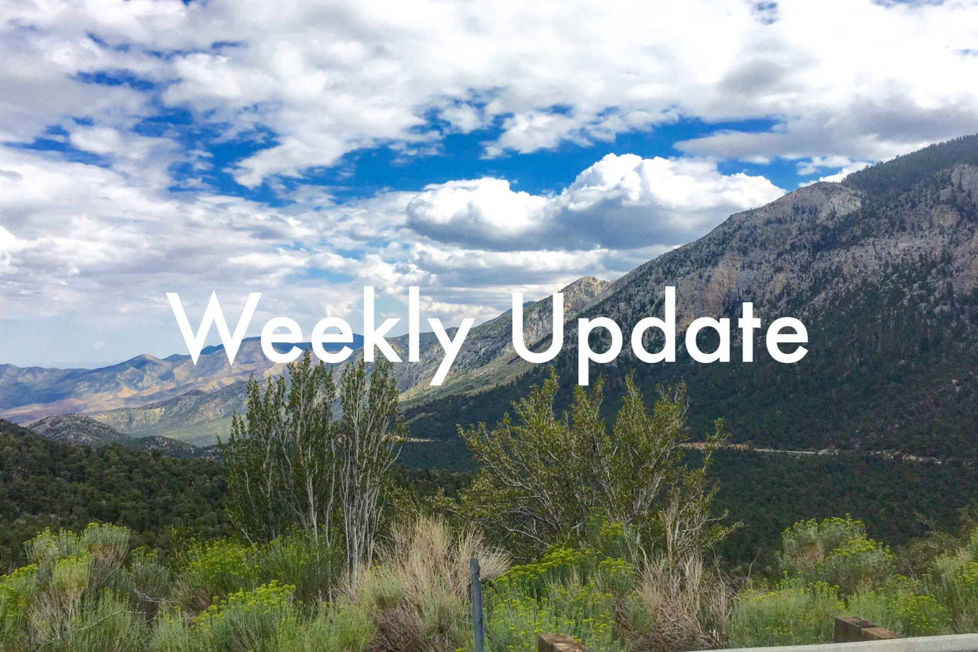 Weekly Update in white text over an expansive mountain vista with highway 158 and puffy clouds in the distance