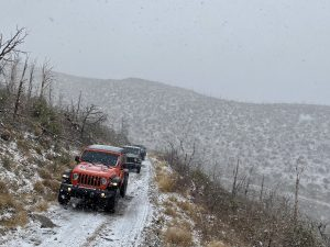 a line of jeeps crawl along a snowy harris mtn rd in the spring mountains