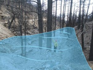blue graphic over man standing in a dry wash showing the high water level of 2013 flood in Harris Springs Canyon