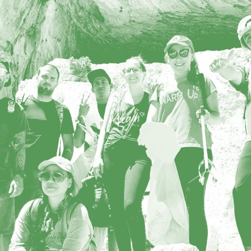 group of volunteers smiling in front of a rocky cave holding trash bags