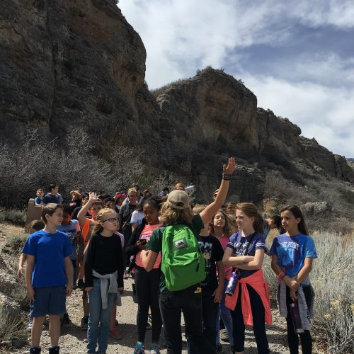 kids raising hands and answering questions of the guided hike leader on dry mountain trail