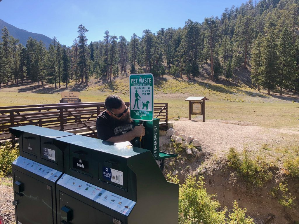 Volunteer installs new pet waste station at Lee Meadows