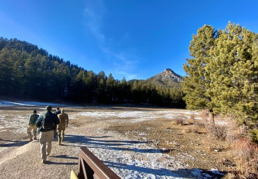 Group of men walk into a muddy meadow amid melting snow surrounded by forest and mountains